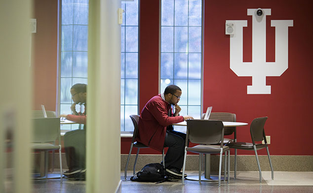 A male student working at a desk on his laptop in front of a big block IU logo on the wall.