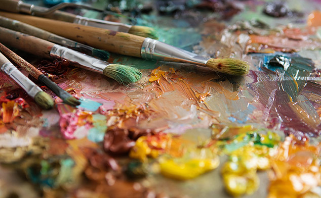 Used artist paint brushes laying on a colorful palate.