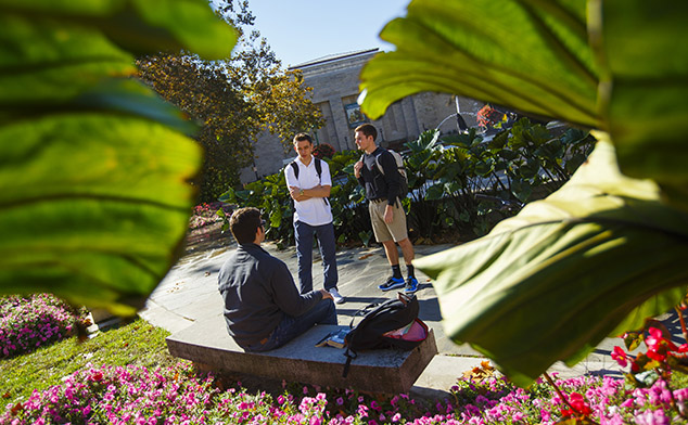 Peek-a-boo style photo of three male students talking with the IU Auditorium in the background.