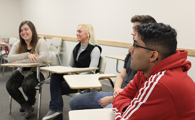 A group of students intently listening in a class discussion session.