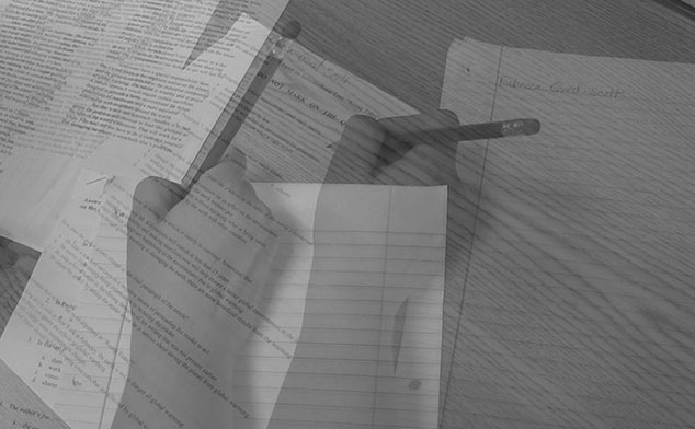Photo of a hand writing on papers.