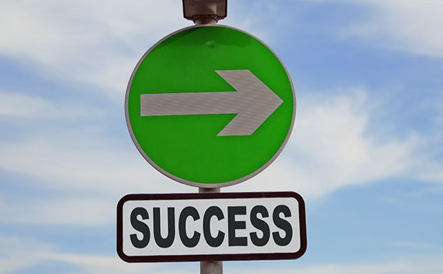 Photo of a sign with an arrow that says Success on it.